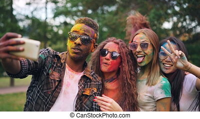 Excited friends girls and guys are taking selfie with colored faces and hair using smartphone, stylish young man is jumping and laughing. Modern technology and party concept.