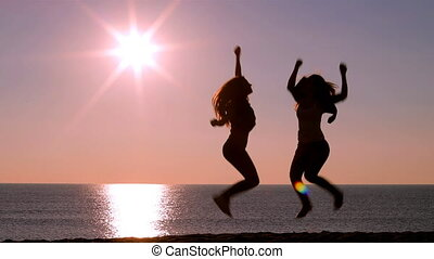 Excited friends jumping at sunrise on the beach - Full body...