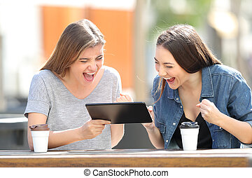 Excited friends watching tablet content in a park