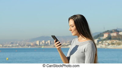 Excited girl celebrating online news on the beach - Side...