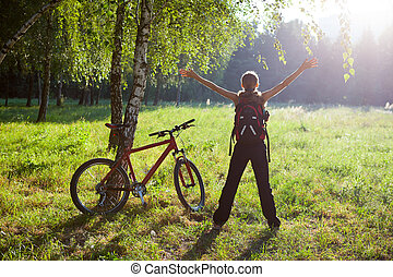 Excited girl cyclist standing in a spring park with hands ...