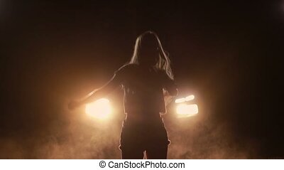 Excited girl dancing in car headlights at night - Young...