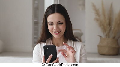 Excited young woman holding smart phone reading good news in social media feed receiving sms message. Overjoyed happy girl user winning auction bid or mobile app game celebrating success concept