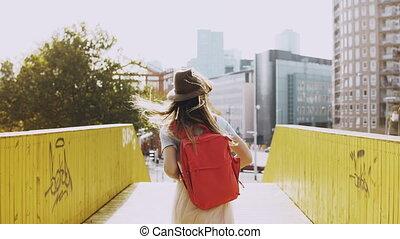 Excited girl in hat, long hair walks on a bridge. European...