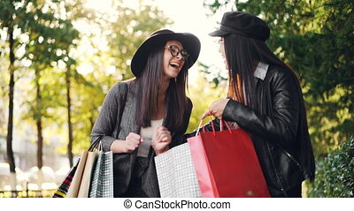 Excited girl is looking at her friend's purchases in bags,...