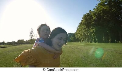 Excited girl laughing on mother's back in park