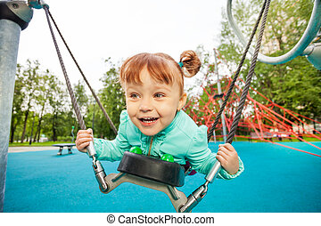 Excited girl on swing holding it with ropes