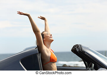 Excited girl on vacation raising arms in a convertible car