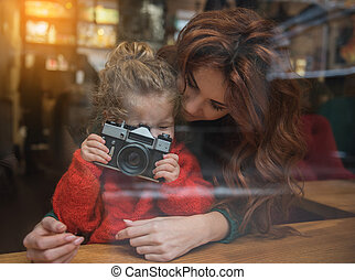 Excited girl photographing while sitting near mom