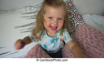Excited girl playing with pillows - Cheerful little girl...