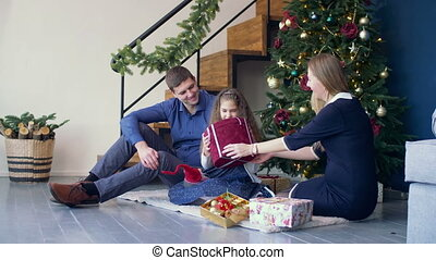 Excited girl receiving christmas gift from parents
