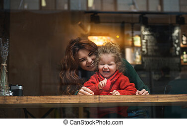 Excited girl sitting near her mom in cafeteria