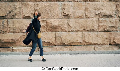 Excited girl student is dancing and singing enjoying music in headphones standing outdoors with stone wall in background. Young woman is holding smartphone.