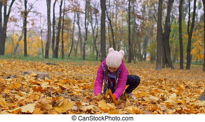 Excited girl throwing fallen autumn foliage in park -...