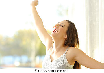 Excited girl waking up in a sunny day
