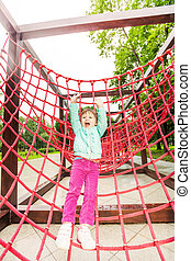 Excited girl with hands up on red net