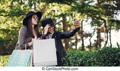 Excited girls are making online video call using smartphone holding device and showing shopping bags with purchases. Communication, technology and fun concept.