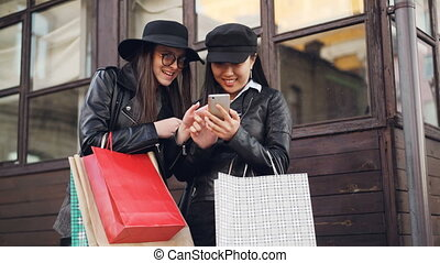 Excited girls are using smartphone touching screen standing in the street and holding shopping bags on autumn day. Modern technology and youth concept.