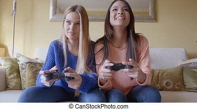 Excited girls playing video games at home