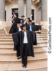 graduates standing outside college building
