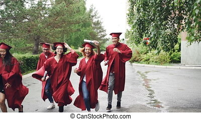 Excited graduating students are running with diplomas on...