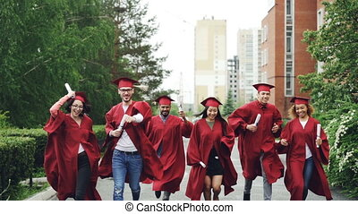 Excited graduating students running along road on campus...