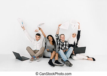 Excited group of four multiethnic friends keepeing hands raised, sitting together on the floor on white background, and happy after successful project or passed exam