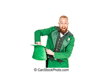 excited handsome man in leprechaun costume holding green hat, isolated on white