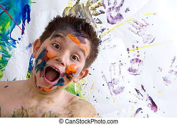 Excited happy little boy doing finger painting standing...