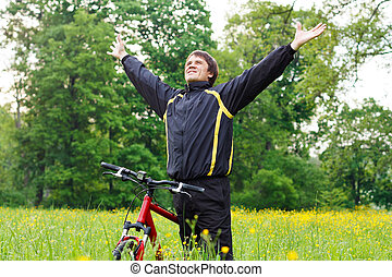 Excited happy man cyclist among the green blooming nature hands outstretched embracing vitality freedom. Outdoor