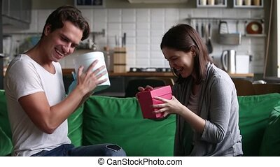 Excited happy young couple exchanging gifts on holiday at...