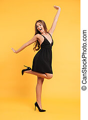 Excited happy young lady in black dress - Photo of excited...