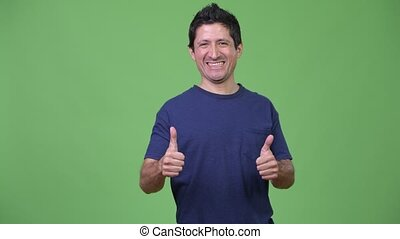 Excited Hispanic man giving two thumbs up - Studio shot of...