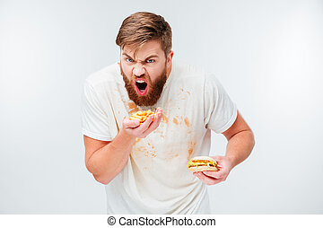 Excited hungry bearded man greedily eating hamburgers
