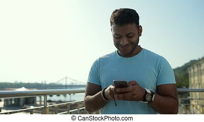 Excited Indian man typing on mobile phone