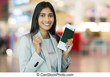 indian woman holding passport and boarding pass - excited...