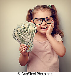Excited kid girl earring money and thinking how spend its. ...