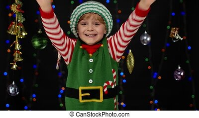 Surprised excited kid girl in Christmas elf Santa Claus helper costume doing winner gesture, say Yes isolated on black background with garland. Child wow effect. People New Year holidays celebration