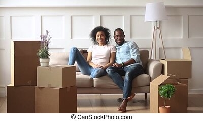 Excited little african kids holding boxes playing in living room