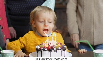 Excited little boy blowing candles on his birthday