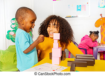 Excited little boy in nursery about block tower