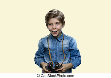 Excited little boy is holding binoculars.