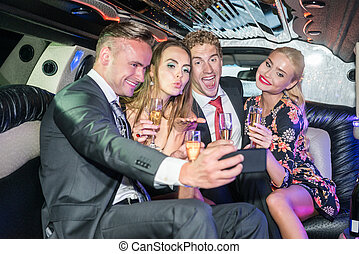 Excited male and female friends with champagne flutes taking selfie from smartphone in limo