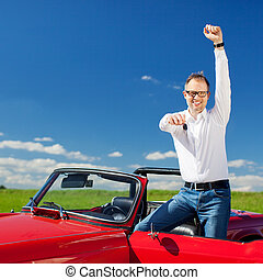 Excited man celebrating ownership of a cabriolet standing with the hood down and door open raising his arm in jubilation and holding out the key in sunny fresh countryside