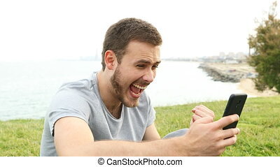 Excited man checking phone messages - Excited man checking...