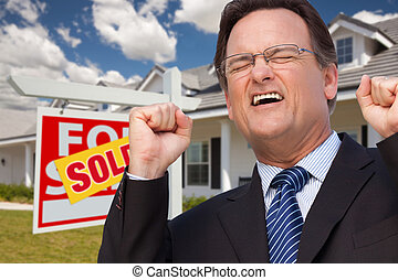 Excited Man in Front of Sold Real Estate Sign and House