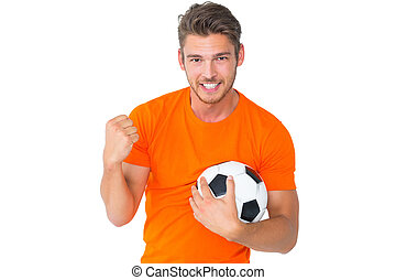 Excited man in orange cheering holding football
