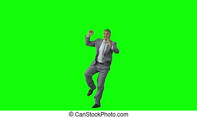 Excited man in slow motion jumping against a green background