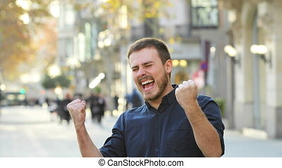 Excited man raising arms in the street - Excited man raising...