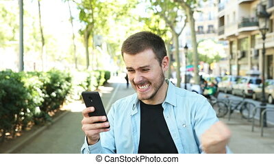 Excited man using phone and looks at camera - Excited man...